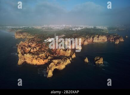 Aerial distant view photo of Ponta da Piedade headland with group of rock formations yellow-golden cliffs along limestone coast, Lagos town Portugal - Stock Photo
