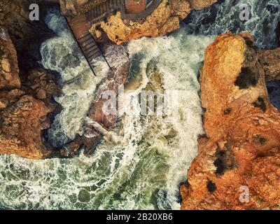 Aerial photo above view Ponta da Piedade headland with group of rock formations yellow-golden cliffs along limestone coastline, Lagos, Portugal - Stock Photo