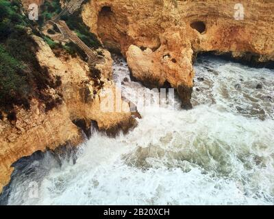 Aerial above view of Ponta da Piedade headland with group of rock formations yellow-golden cliffs along limestone coastline, Lagos town, Portugal - Stock Photo