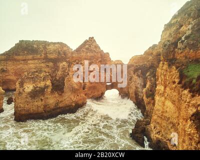 Aerial photo above view of Ponta da Piedade headland with group of rock formations yellow-golden cliffs along limestone coastline, Lagos town Portugal - Stock Photo
