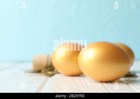 Golden eggs and money on against blue background, space for text