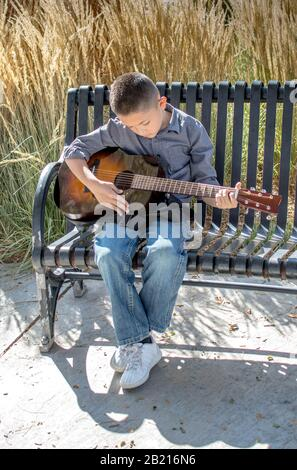 A young boy practices his acoustic guitar outdoors on a beautiful fall day