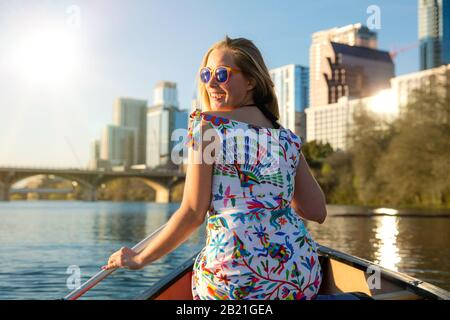 Happy, joyful, cheerful young woman in sunglasses enjoying a hot summer day with water activities, boating, kayaking, and canoeing in Austin Texas Stock Photo