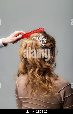 Wave curls hairstyle. Hairdresser making hairstyle to blond hair woman with long hair using comb on gray background. Professional hairdressing