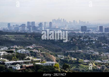 Canyon homes with hazy smoggy cityscape view of Century City and Downtown Los Angeles skylines.