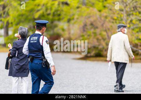 Kyoto, Japan - April 17, 2019: Courtyard exterior in Imperial Palace with guard police officer security walking on garden road by tourists - Stock Photo
