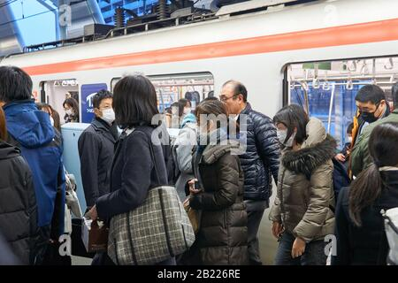 Japanese people wearing surgical masks to prevent infection by the novel coronavirus (COVID-19) exit trains at Tsukuba Express's Moriya Station. - Stock Photo