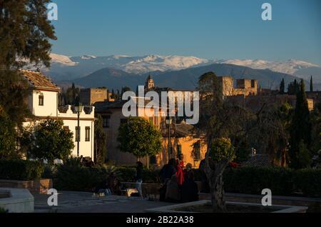 Granada, Spain - January 6, 2017: People observe Alhambra palace from Placeta Cristo de las Azuzenas viewpoint in Granada, Spain - Stock Photo