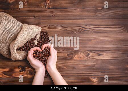 Roasted coffee beans waking up from a jute coffee bag on an old wooden table. Close-up. Female palms folded in the shape of a heart, copyspace. - Stock Photo