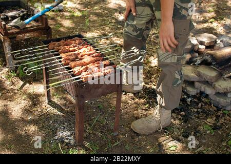 Marinated shashlik preparing on a barbecue grill over charcoal - Stock Photo