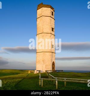 Exterior of old sunlit Flamborough Head Lighthouse (historic tall white chalk octagonal beacon tower) & deep blue sky - near Bridlington, England, UK.