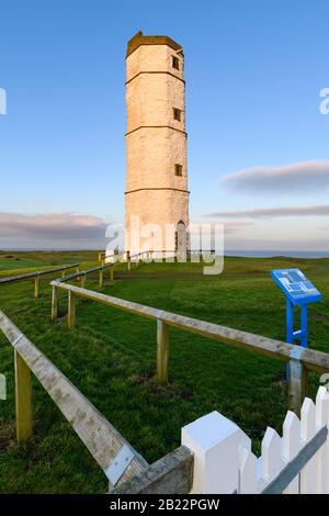 Exterior of old sunlit Flamborough Head Lighthouse (historic tall white chalk octagonal beacon tower) & deep blue sky - Yorkshire Coast, England, UK.