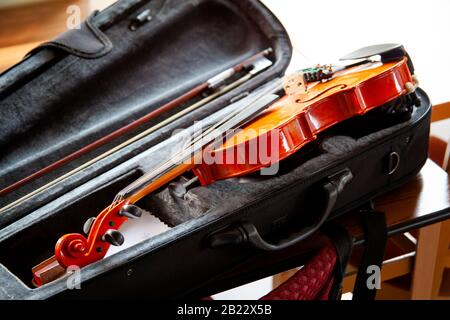 Violin with a bow laying in an open black fiddle case on the table. Classical musical string instruments group concept, nobody. Safe instrument