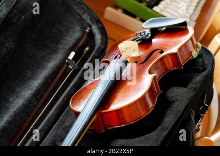 Violin, fiddle with a bow laying in an open black case on the table, small xylophone in the back. Simple classical musical string instruments group