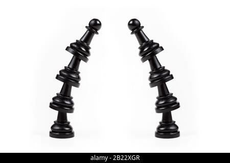 Two leaning crooked bent towers of black chess pawns forming a gate frame Passage, arch, door, border made from game pieces, copy space in the middle - Stock Photo