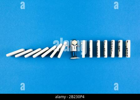 stickman figure preventing line of domino tiles from falling, domino effect and event chain concept - Stock Photo
