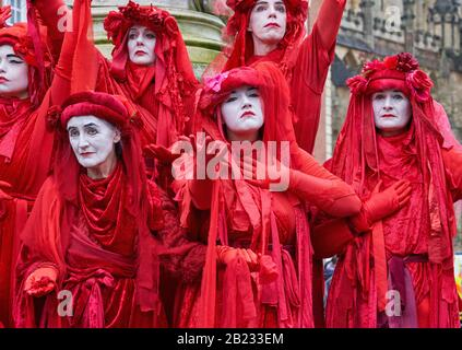 The Red Brigade of Extinction Rebellion displaying their striking poses in peaceful protest supporting action on climate change - Bristol UK
