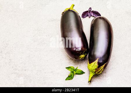 Fresh organic eggplants. Healthy vegan (vegetarian) cooking concept. With basil leaves on stone concrete background, copy space Stock Photo