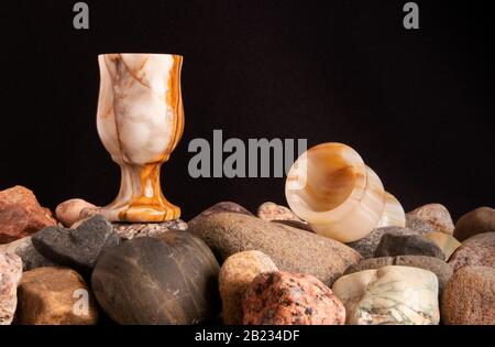 Still life with two onyx glasses on a pile of pebble and shells against black fabric - Stock Photo
