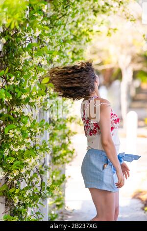 Young adult woman girl person spinning turning motion in summer on sunny day in garden vine plant flowers outside gardening and wearing pastel fashion