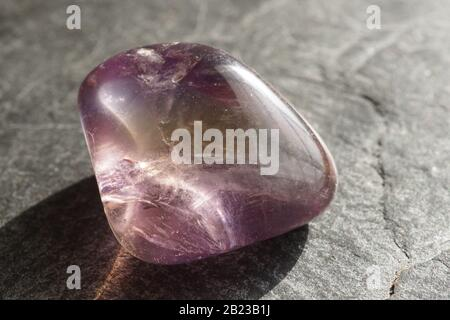 Ametrine tumbled pebble on gray slate background, lit by the sun - Stock Photo