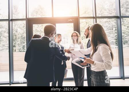 Multi ethnic business people, entrepreneur, business, small business concept. Group of business people busy discussing financial matter during meeting