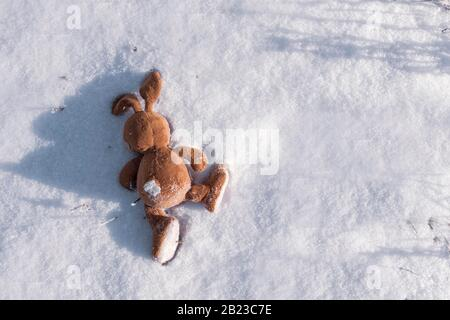 abandoned Bunny toy lies on the snow. Copyspace. Children lose and throw toys. Allegory, separation, loneliness, and death.
