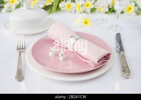 Classic serving for a Easter dinner with white and pink porcelain plates, pink napkin, silverware, two Easter rabbits and spring flowers are on a whit - Stock Photo