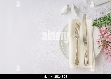 Classic serving for a gala dinner with luxurious porcelain, silverware and spring flowers on a white tablecloth, with copy-space, top view - Stock Photo