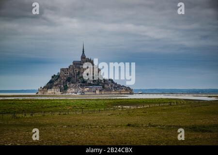 View of famous Le Mont Saint-Michel tidal island. Green field in the foreground