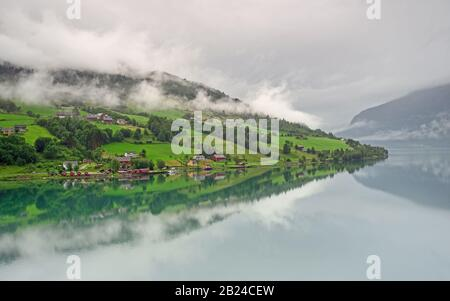 Reflections in the Nordfjorden on a cloudy day at Olden, Norway. - Stock Photo