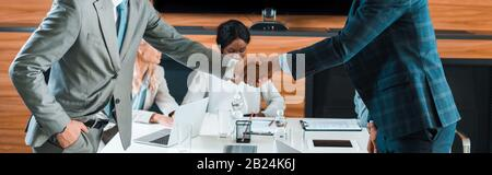 cropped view of two businessmen shaking hands near multicultural colleagues sitting in conference hall - Stock Photo