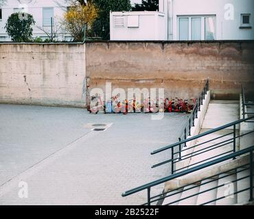 Multiple kinder playing toys machines in courtyard of French kindergarten - Stock Photo