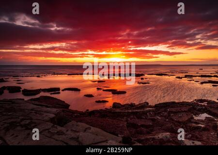 The sky clears after a rain storm just long enough to show the deep red and purple clouds over the South Dorset jurassic coastline - Stock Photo