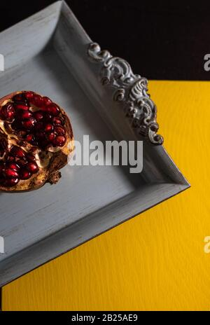 Minimalism art photo half of pomegranate on squared blue dish on yellow and black background. Top view with copy space. - Stock Photo