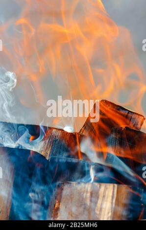 Smoke and fire from burning logs. Close up. Vertical photo - Stock Photo