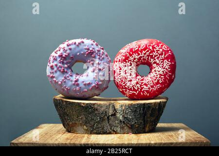 two round glazed donuts sprinkled with sweet icing red and purple on a wooden base on gray background. sweet bun on a decorative forest stand. - Stock Photo