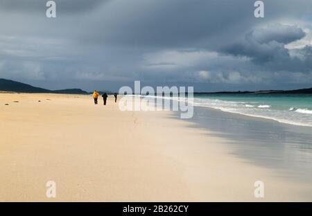 Walkers on Traigh Rosamol Beach with dark cloudy skies above, Luskentyre Beach, Isle of Harris, Scotland, UK