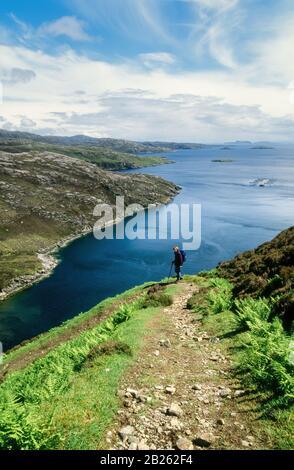 Lone adult female hill walker on rough footpath high above Loch Trolamaraig, Isle of Harris, Outer Hebrides, Scotland, UK - Stock Photo