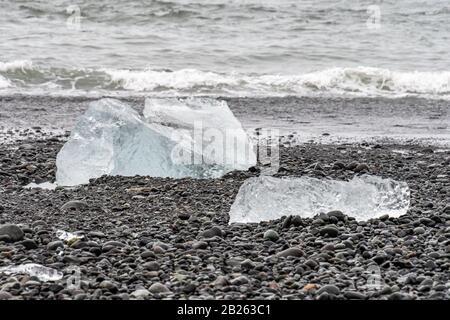 Diamond beach black sand crystal clear pieces of ice lying on dark rocks - Stock Photo