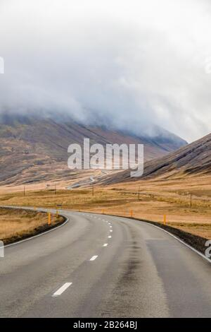 Northern Iceland empty road winding through valley upwards a mountain during unpleasant grey weather - Stock Photo