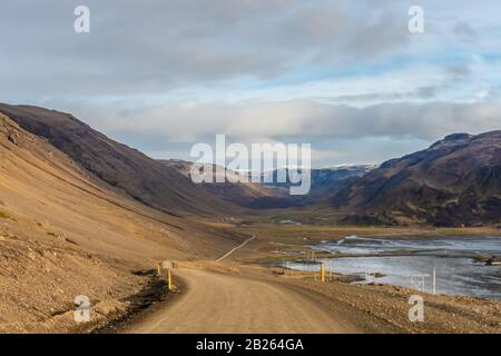 Road trip in Iceland dirt road in west iceland winding down into fjord during sunny weather - Stock Photo