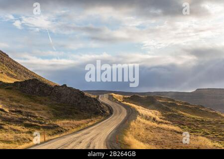 Road trip in Iceland dirt road in west iceland winding along atlantic coast during beautiful sunshine - Stock Photo