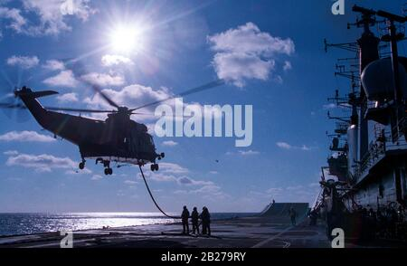 The Royal Navy aircraft carrier HMS Invincible in the LPH (Landing Platform Helicopter), assualt role. A Sea King HC4 helicopter being refuelled whilst airborne from the flight deck. - Stock Photo