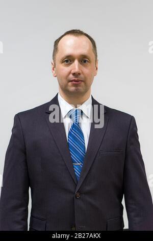 portrait of a confident, purposeful, successful businessman weared in grey suit and blue neck tie