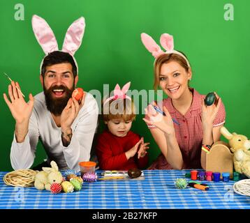 Mother, father and son painting eggs in pink bunny ears. Happy moments and Easter celebration concept. Family members preparing for Easter on green background. Man and woman with happy smiles.