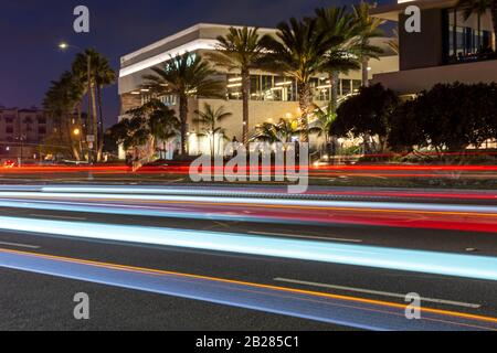 Colorful light trails on a city road in front of illuminated buildings at night.