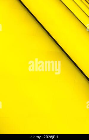 Yellow abstract background with dark diagonal lines. Fondation Louis Vuitton, Paris, France, July 2019. Beautiful design, colorful vertical shot. Stock Photo