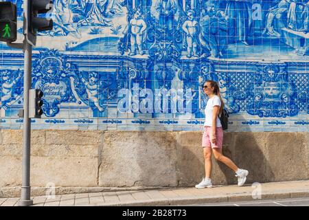 Beautiful women walking along Capela Rua de Santa Catarina church and enjoying view. Summer travel destination. Portugal, Porto, 17.08.2019 - Stock Photo