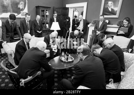 Washington, United States Of America. 26th Feb, 2020. Vice President Mike Pence and members of the PresidentÕs Coronavirus Task Force bow their heads in prayer during a meeting Wednesday, February 26, 2020, in his West Wing Office of the White House People: Vice President Mike Pence Credit: Storms Media Group/Alamy Live News - Stock Photo